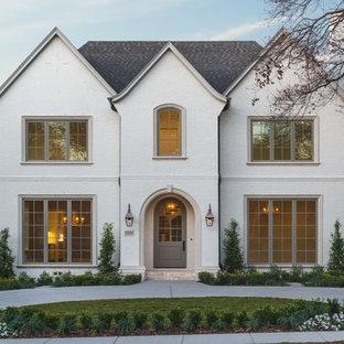 Ejemplo de fachada blanca, clásica, de dos plantas, con revestimiento de ladrillo y tejado a dos aguas