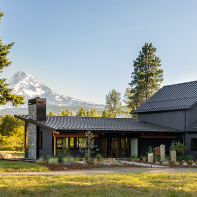 Inspiration for a large rustic black one-story wood house exterior remodel in Portland with a shed roof and a metal roof