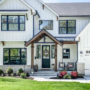 Пример оригинального дизайна: двухэтажный, белый частный загородный дом среднего размера в стиле кантри с облицовкой из ЦСП и металлической крышей