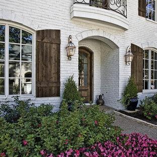 Modelo de fachada blanca, mediterránea, de tamaño medio, de dos plantas, con revestimiento de ladrillo