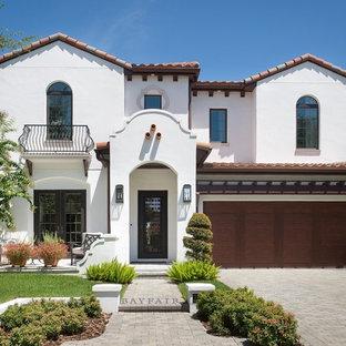 Diseño de fachada de casa blanca, mediterránea, de tamaño medio, de dos plantas, con revestimiento de estuco, tejado a dos aguas y tejado de teja de barro