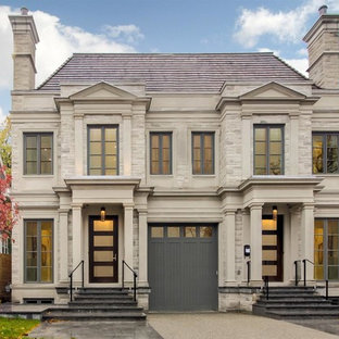 Design ideas for a traditional two-storey duplex exterior in Toronto with a hip roof and stone veneer.