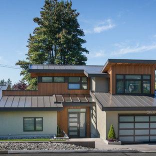 Ejemplo de fachada de casa multicolor, contemporánea, de tamaño medio, de dos plantas, con tejado de metal, revestimientos combinados y tejado a dos aguas