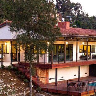 Diseño de fachada de casa blanca, ecléctica, grande, de dos plantas, con revestimiento de estuco, tejado a cuatro aguas y tejado de teja de barro