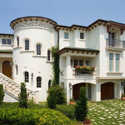 Mid-sized tuscan white three-story stucco exterior home photo in Tampa with a tile roof