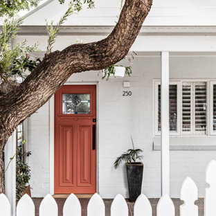 Design ideas for a small scandinavian one-storey brick white house exterior in Sydney with a gable roof and a metal roof.