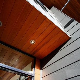 Ejemplo de fachada gris, retro, grande, de dos plantas, con revestimiento de madera y tejado a dos aguas