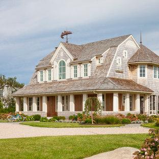 Diseño de fachada de casa beige, marinera, grande, de dos plantas, con tejado a doble faldón, revestimiento de madera y tejado de teja de madera