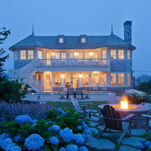 Пример оригинального дизайна: большой, деревянный, двухэтажный, бежевый частный загородный дом в викторианском стиле с крышей из гибкой черепицы