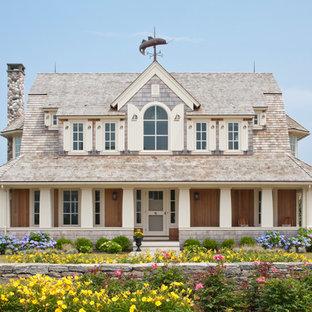 Modelo de fachada de casa beige, costera, grande, de dos plantas, con revestimiento de madera y tejado de teja de madera