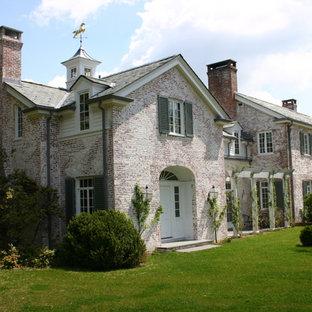 Immagine della facciata di una casa classica a due piani con rivestimento in mattoni