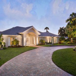 Bild på ett mellanstort funkis beige hus, med allt i ett plan, stuckatur och valmat tak