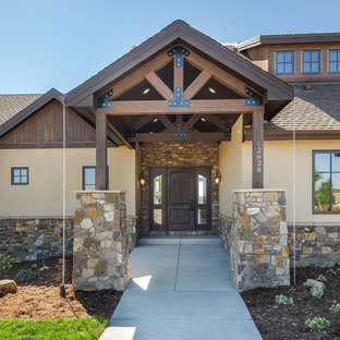Large arts and crafts beige one-story stucco gable roof photo in Denver