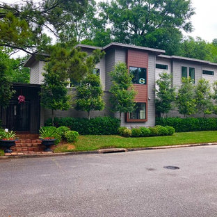 Large transitional orange two-story concrete fiberboard exterior home idea in Houston with a mixed material roof