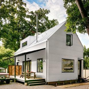 Ejemplo de fachada blanca, de estilo de casa de campo, de dos plantas, con revestimiento de metal y tejado a dos aguas