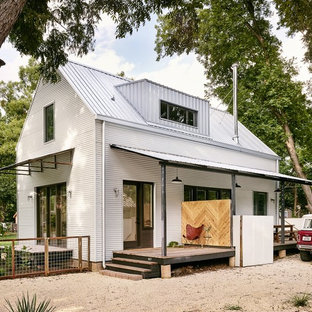 Example of a small farmhouse white two-story metal gable roof design in Austin