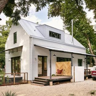 Imagen de fachada blanca, campestre, pequeña, de dos plantas, con revestimiento de metal y tejado a dos aguas