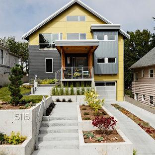 Réalisation d'une façade de maison jaune design avec un toit à deux pans.