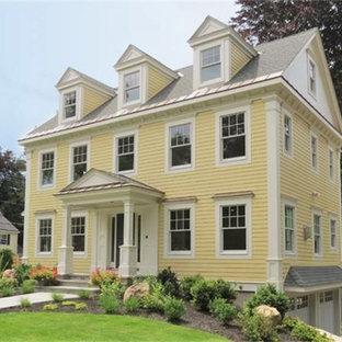 Inredning av ett klassiskt stort gult hus, med tre eller fler plan, sadeltak och tak i mixade material