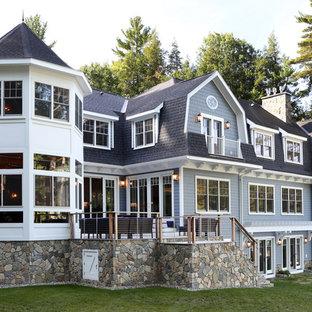 Inspiration pour une très grand façade de maison bleue traditionnelle à deux étages et plus avec un toit de Gambrel, un revêtement en panneau de béton fibré et un toit en shingle.