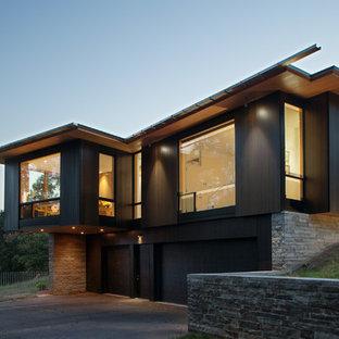Diseño de fachada de casa negra, minimalista, de dos plantas, con revestimiento de madera y tejado de un solo tendido