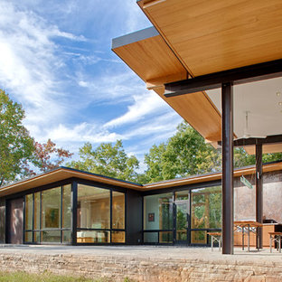 Example of a minimalist black metal house exterior design in Charlotte with a shed roof