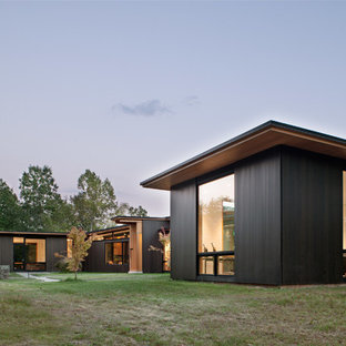 Example of a minimalist black one-story wood house exterior design in Charlotte with a shed roof