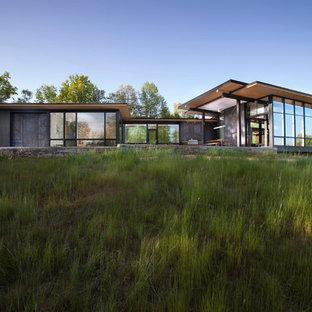 Ispirazione per la facciata di una casa unifamiliare nera moderna a un piano con rivestimento in vetro e tetto a una falda