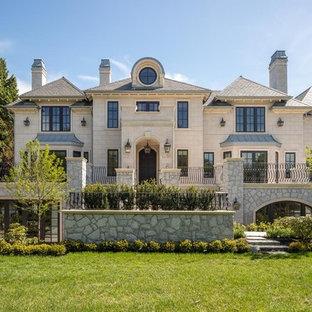 Imagen de fachada de casa beige, romántica, grande, de tres plantas, con revestimiento de piedra, tejado a cuatro aguas y tejado de teja de madera