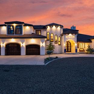 Ejemplo de fachada de casa blanca, mediterránea, de dos plantas, con revestimiento de estuco, tejado a cuatro aguas y tejado de teja de barro