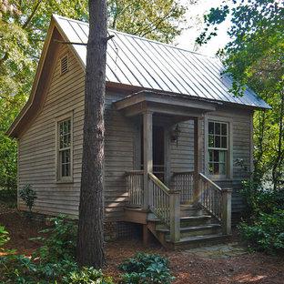 Esempio della facciata di una casa piccola rustica con rivestimento in legno e tetto a capanna