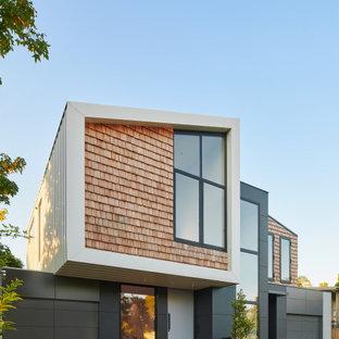 Foto på ett mellanstort funkis svart hus, med två våningar, sadeltak och tak i metall