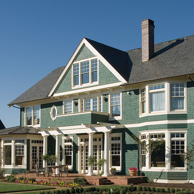 Large elegant green three-story wood exterior home photo in St Louis
