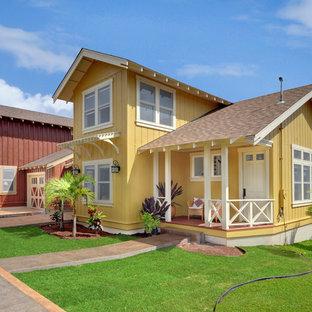 Inspiration pour une façade de maison jaune ethnique de taille moyenne et à un étage avec un toit à deux pans et un toit en shingle.