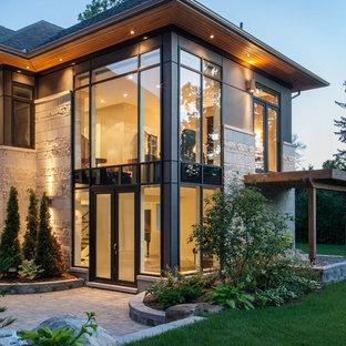 Contemporary gray two-story stone exterior home idea in Ottawa