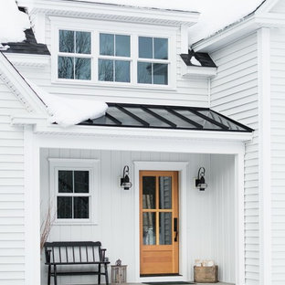 Пример оригинального дизайна: двухэтажный, белый частный загородный дом среднего размера в стиле кантри с облицовкой из винила, двускатной крышей и крышей из смешанных материалов