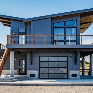 На фото: трехэтажный, синий дом в современном стиле с крышей-бабочкой