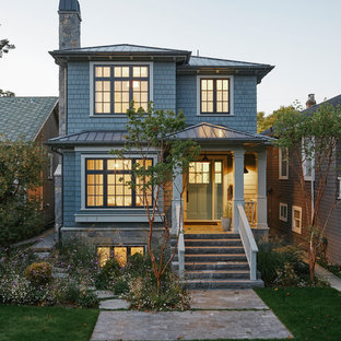 Mid-sized traditional two-storey blue house exterior in Vancouver with wood siding, a hip roof and a metal roof.