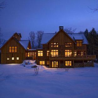 Idee per la facciata di una casa unifamiliare ampia rustica a tre piani con rivestimento in legno, tetto a capanna e copertura in metallo o lamiera