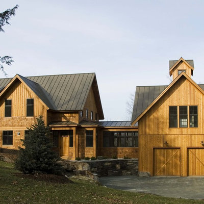Inspiration for a country three-story wood exterior home remodel in Burlington with a metal roof