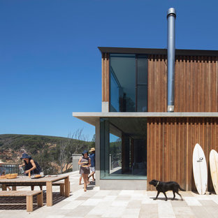 Beach style brown two-story wood house exterior idea in Los Angeles with a shed roof and a metal roof