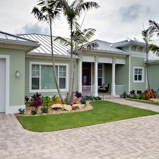Example of a mid-sized island style green one-story stucco exterior home design in Miami