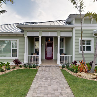 Example of a mid-sized island style green one-story exterior home design in Miami