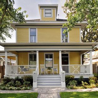 Immagine della facciata di una casa gialla classica con rivestimento in legno