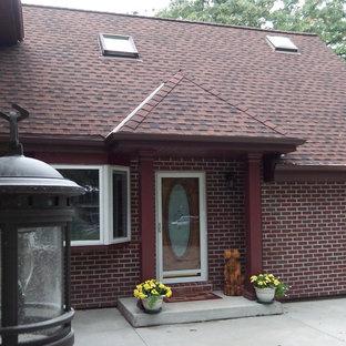 Imagen de fachada roja, bohemia, pequeña, de una planta, con revestimiento de ladrillo y tejado a cuatro aguas