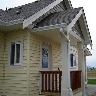 Immagine della facciata di una casa unifamiliare piccola gialla country a un piano con rivestimento in vinile, tetto a capanna e copertura a scandole
