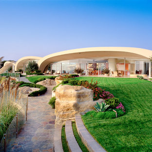 Inspiration for a large eclectic beige one-story glass exterior home remodel in Orange County