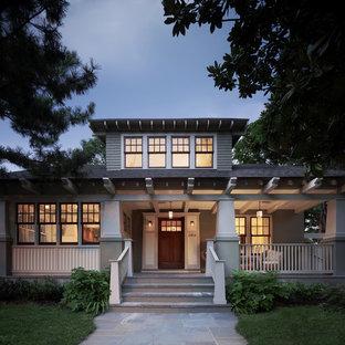 На фото: двухэтажный, зеленый дом в стиле кантри с