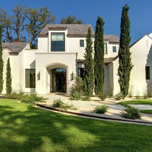 На фото: двухэтажный, белый дом в средиземноморском стиле с облицовкой из цементной штукатурки и мансардной крышей с