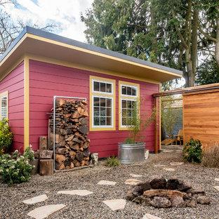 Ejemplo de fachada de casa roja, ecléctica, pequeña, de una planta, con revestimientos combinados, tejado de un solo tendido y tejado de metal